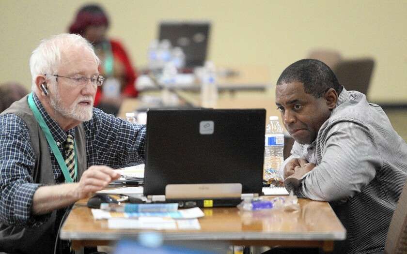 Mike Everding, left, helps James Randle sign up for a Covered California plan at an enrollment event in March in Inglewood.