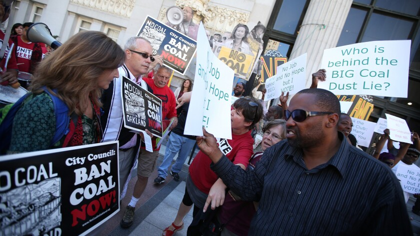 Pro-coal demonstrators face off against coal opponents in front of Oakland City Hall on Monday.