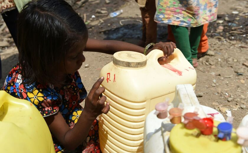A child points to initials on a container on April 28 as she and other villagers line up to collect potable water at a makeshift camp in Mumbai.