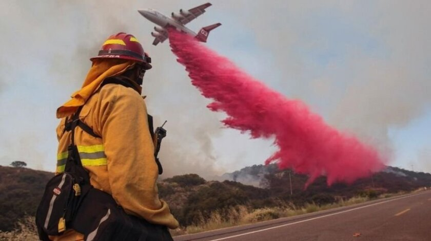 Upland Fire Capt. Joe Burna watches as a tanker drops fire retardant to stop a wildfire from jumping over Highway 94 near Potrero, Calif. in June.