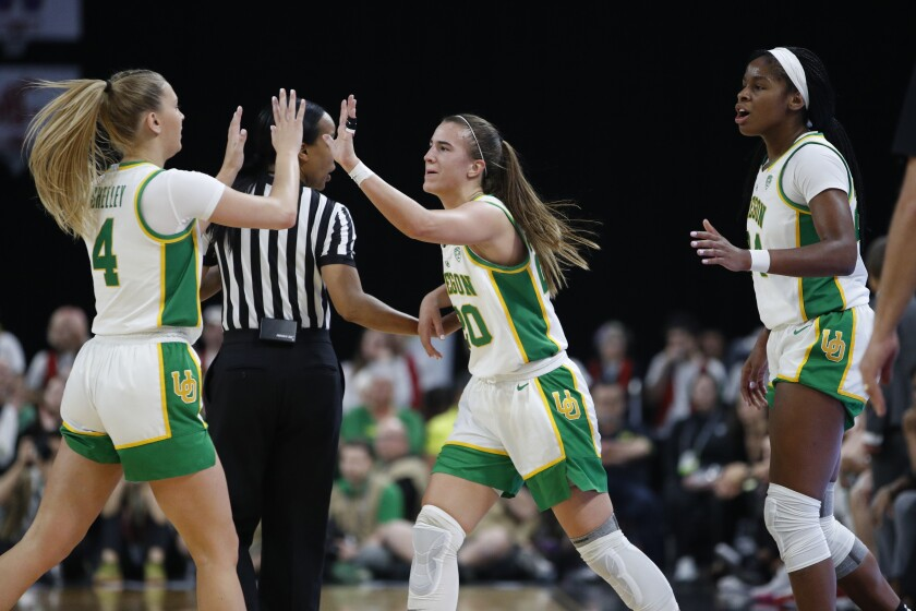 Oregon's Sabrina Ionescu, center, celebrates with Jaz Shelley, left, and Ruthy Hebard, right, during the first half of an NCAA college basketball game against Stanford in the final of the Pac-12 women's tournament Sunday, March 8, 2020, in Las Vegas. (AP Photo/John Locher)