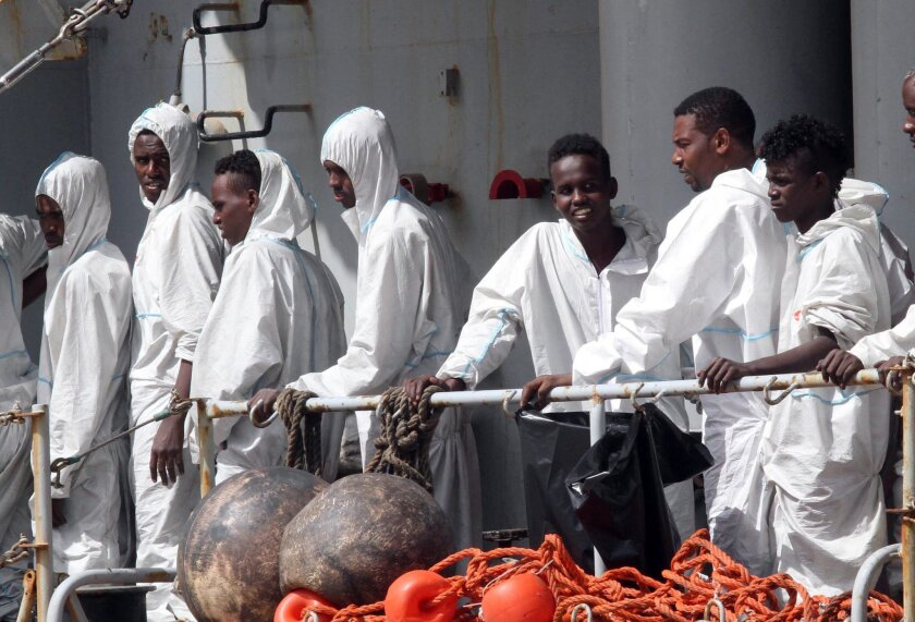 In this photo taken Sunday, May 29, 2016 migrants attend to disembark from the Italian Navy Vega vessel, in Reggio Calabria, southern Italy, after being rescued in the Mediterranean Sea off the coasts of Libya. Survivor accounts have pushed to more than 700 the number of migrants feared dead in Med