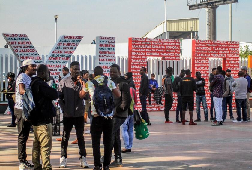 Migrantes de diversas nacionalidades esperan en la plaza cívica de Tijuana