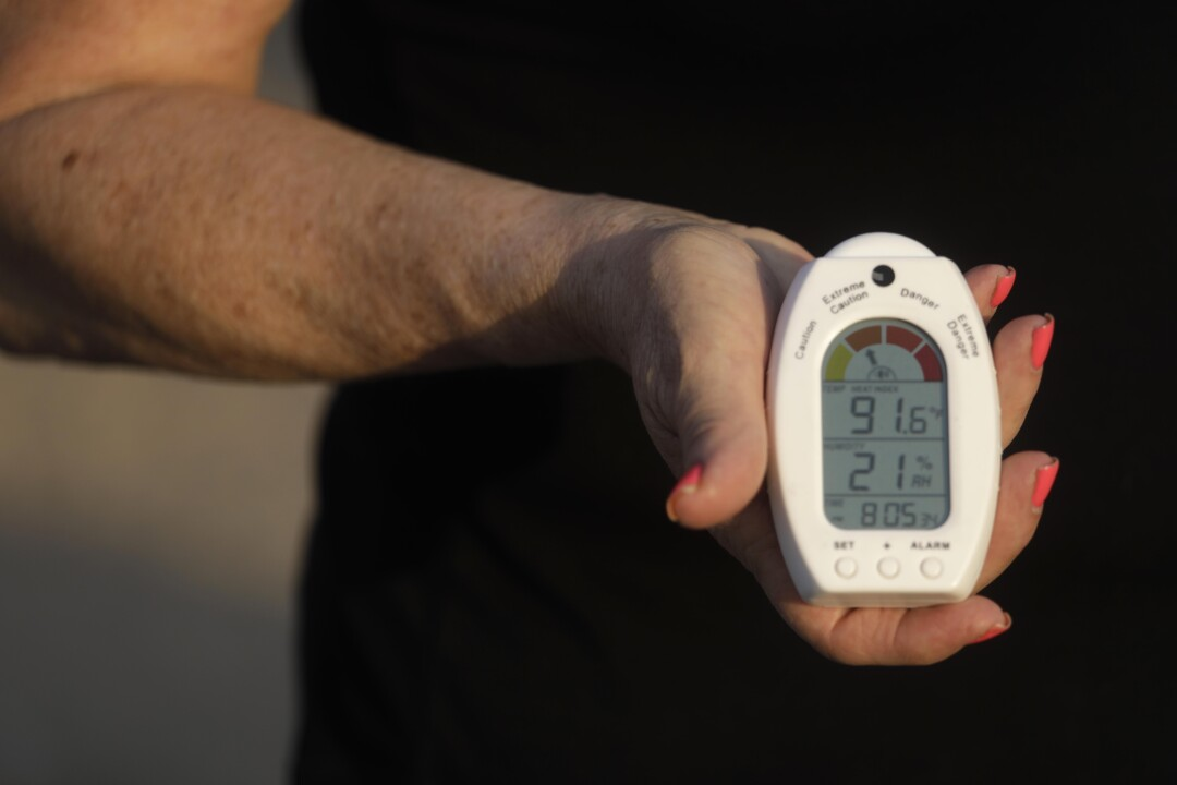 A woman's hand holds a thermometer with a display showing an outdoor reading of 91.6 degrees