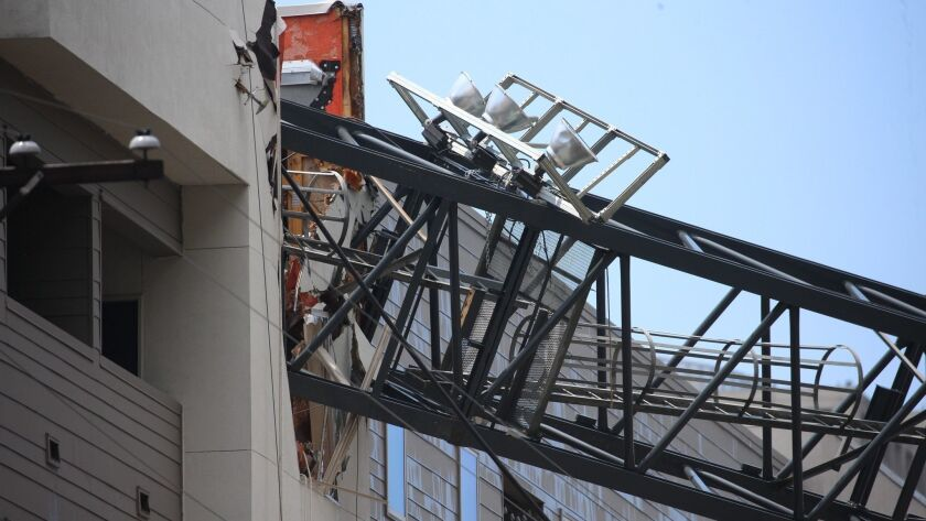 Officials respond to the scene after a crane collapsed into Elan City Lights apartments amid severe