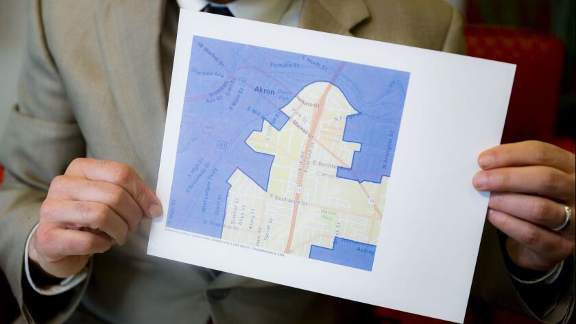 David Niven, a professor of political science at the University of Cincinnati, holds a map illustrating a gerrymandered Ohio district on April 11.