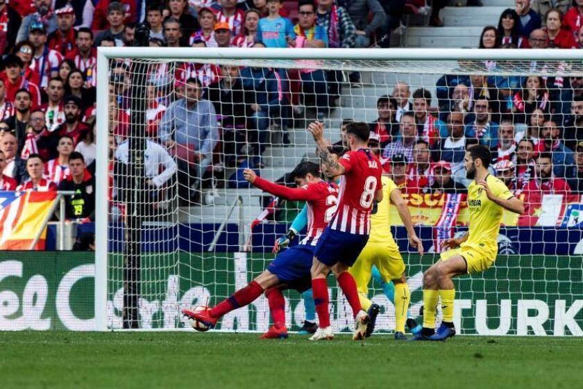 El delantero del Atlético de Madrid Álvaro Morata (i) lanza y marca gol ante el Villarreal, el primero del equipo, durante el partido de la vigésimo quinta joranda de Ligaen el estadio Wanda Metropolitano de Madrid . EFE