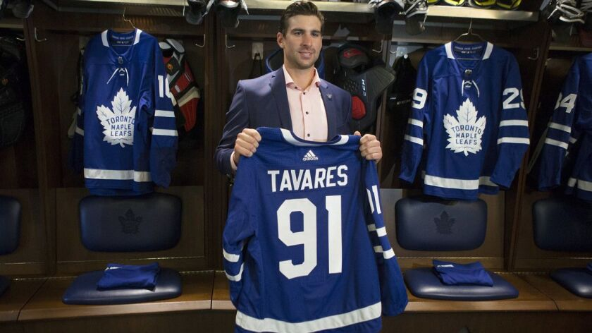 John Tavares holds up a Maple Leafs jersey in the Maple Leafs' locker room following a news conferen