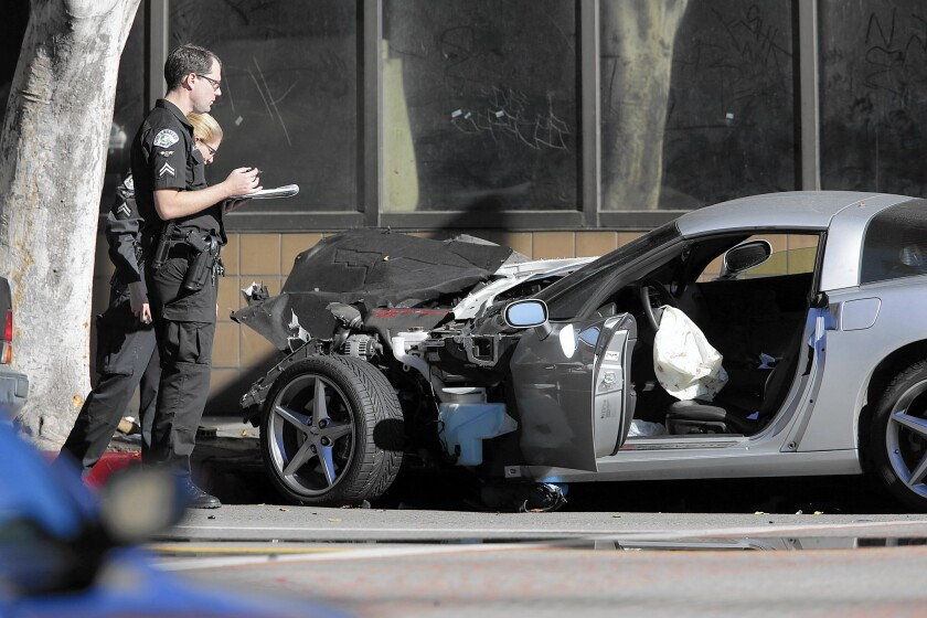 Police investigators at the scene where a silver Corvette crashed during an LAPD chase.