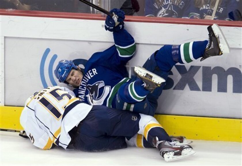 Vancouver Canucks defenseman Kevin Bieksa (3) goes into the boards with Nashville Predators center Craig Smith (15) during the second period of their NHL hockey game, Thursday, March,14, 2013, in Vancouver. (AP Photo/The Canadian Press, Jonathan Hayward)