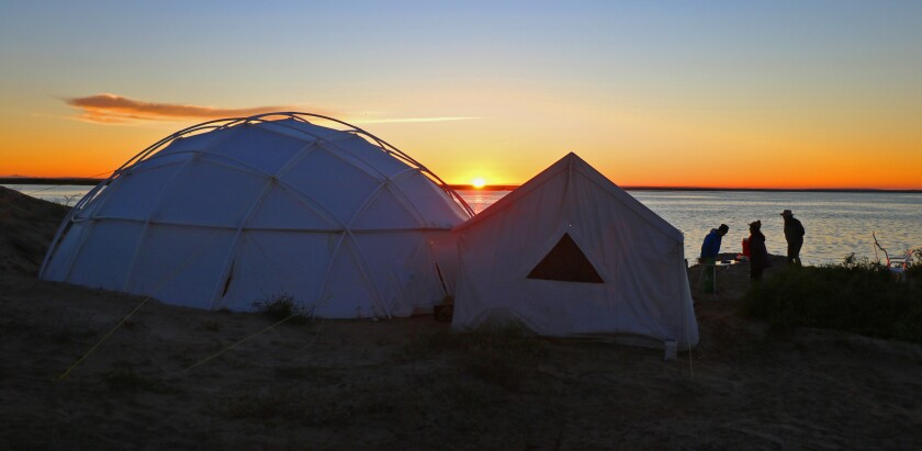In the morning coolness, the sun rises over the yurt and cook tent.