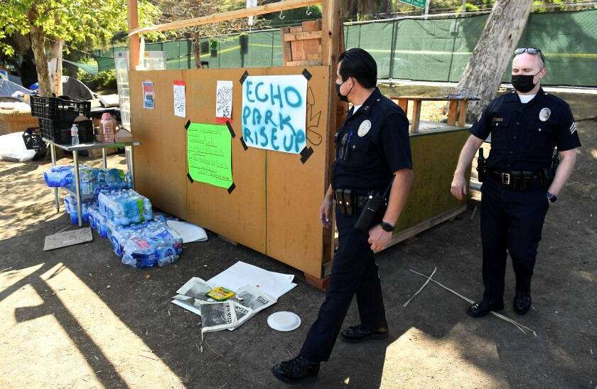 LAPD officers Adrian Gonzalez, left, and Sgt. Matt Jacobs at the remains of the encampment in Echo Park.