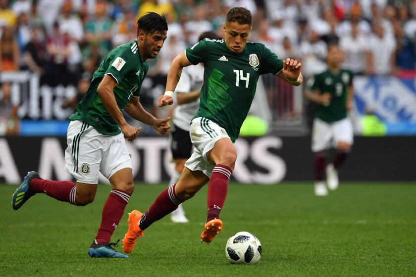 """Mexico's Javier """"Chicharito"""" Hernández, right, drives the ball past forward Carlos Vela during the 2018 World Cup."""