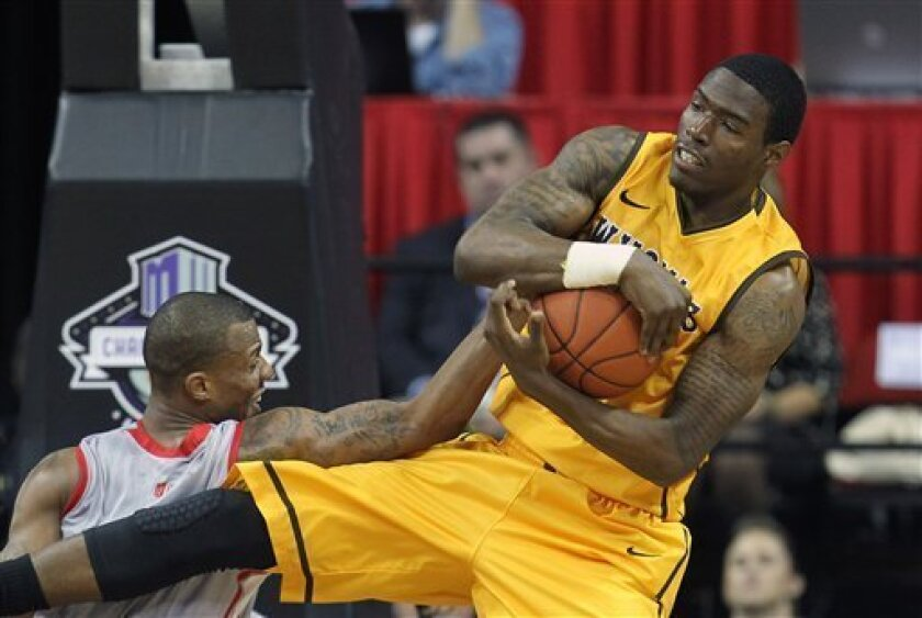 Wyoming's Derek Cooke Jr. and New Mexico's Chad Adams go after a rebound during the second half of a Mountain West Conference tournament NCAA college basketball game on Wednesday, March 13, 2013, in Las Vegas. New Mexico defeated Wyoming 59-46. (AP Photo/Isaac Brekken)