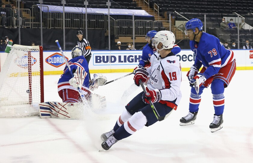 Nicklas Backstrom, center, of the Washington Capitals scores in the third period against Igor Shesterkin, left, of the New York Rangers during an NHL hockey game Monday, May 3, 2021, in New York. (Bruce Bennett/Pool Photo via AP)