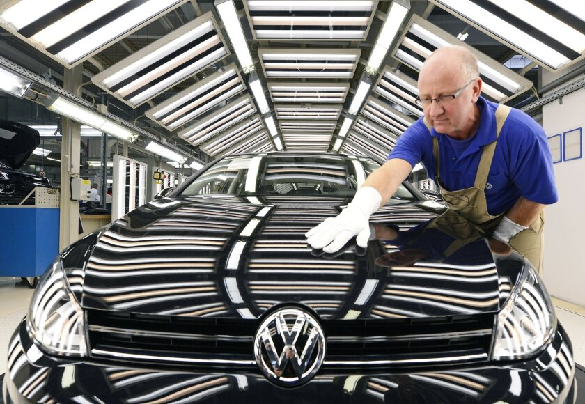 FILE - In this Nov. 9, 2012 file photo worker Michael Keil checks a Golf VII car during a press tour at the plant of the German car manufacturer Volkswagen AG (VW) in Zwickau, central Germany. Volkswagen AG says Wednesday, July 29, 2015, that profits slipped by 16 percent in the second quarter. (AP Photo/Jens Meyer,File)