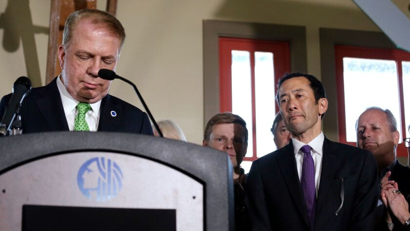 Seattle Mayor Ed Murray, left, reads a statement to media and supporters, as his husband Michael Shi