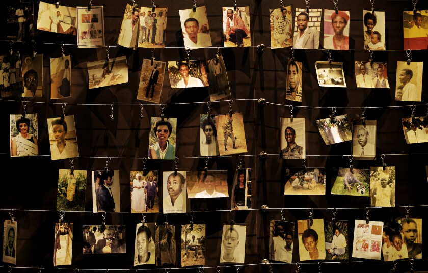 Photographs of Rwanda genocide victims, clipped to wires, hang in rows.