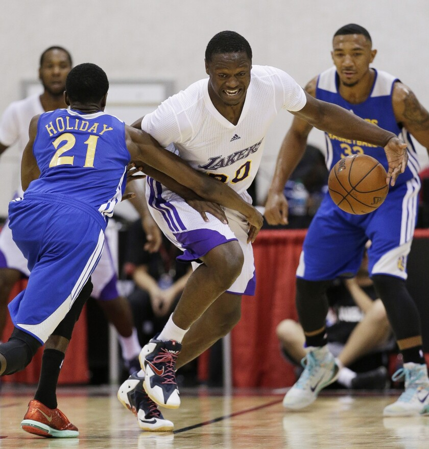 Julius Randle drives up the court against the Golden State Warriors' Justin Holiday during a July 14 NBA summer league game in Las Vegas.