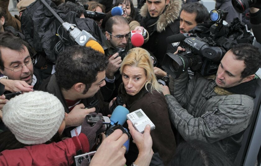 FILE - In this December 22, 2010 file photo, Spain's dormer world steeplechase champion Marta Dominguez, center, reacts as she is surrounded by reporters after leaving a court house in Madrid, Spain. Spain's Sports Council has stripped runner Marta Dominguez of her status as a Spanish athlete after