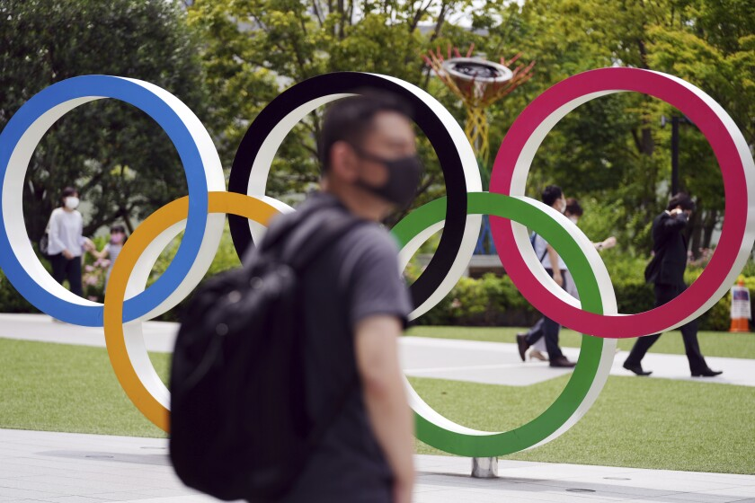 People walk near the Olympic Rings Wednesday, June 2, 2021, in Tokyo. Roads are being closed off around Tokyo Olympic venues including the new $1.4 billion National Stadium where the opening ceremony is set for July 23. (AP Photo/Eugene Hoshiko)