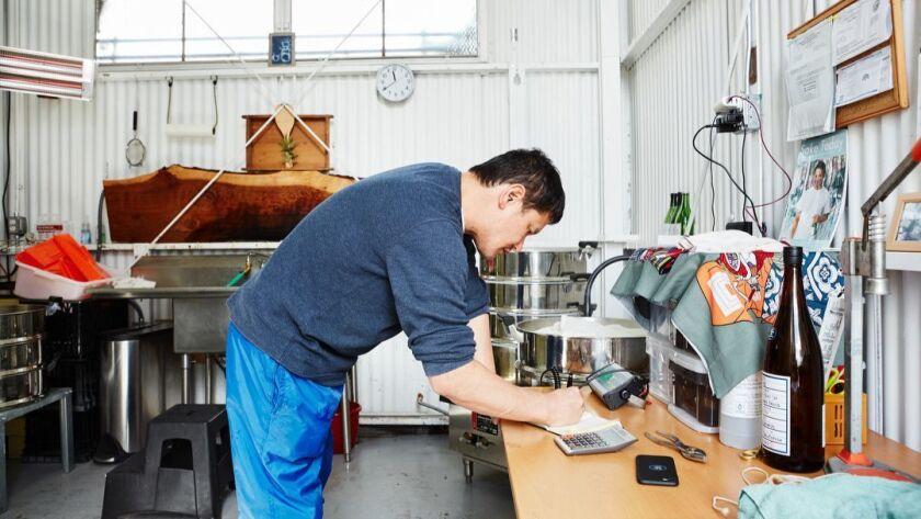Oakland, CA - March 9, 2019: Yoshihiro Sako weighs steamed rice to brew sake at Den Sake Brewery.
