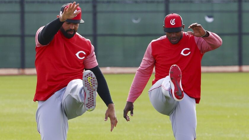 Cincinnati Reds' Matt Kemp, left, and Yasiel Puig, right, stretch out with their new teammates at the Reds spring training baseball facility Monday, Feb. 18, 2019, in Goodyear, Ariz.