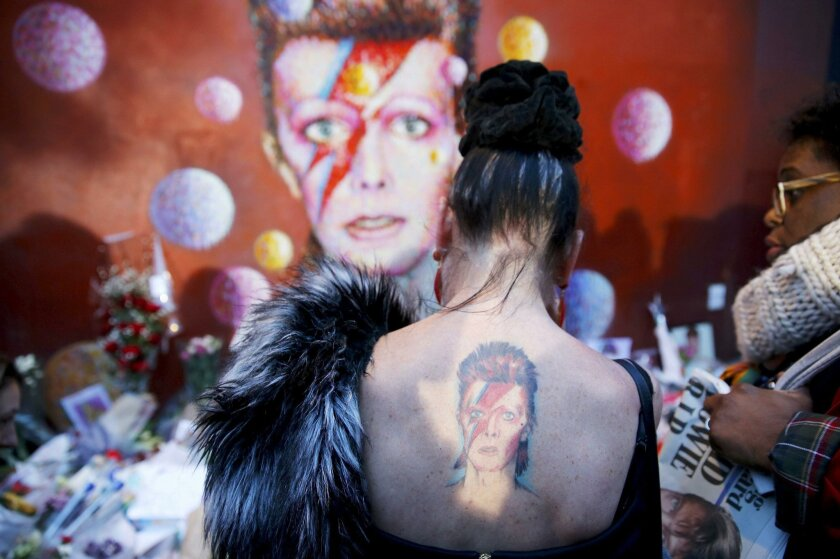"""A woman with a Ziggy Stardust tattoo visits a mural of David Bowie in Brixton, south London, January 11, 2016. David Bowie, a music legend who used daringly androgynous displays of sexuality and glittering costumes to frame legendary rock hits """"Ziggy Stardust"""" and """"Space Oddity"""", has died of cancer"""