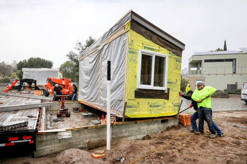 Workers from San Diego based Modulartech maneuver a student-built cottage at a Wounded Warrior Homes in Vista.