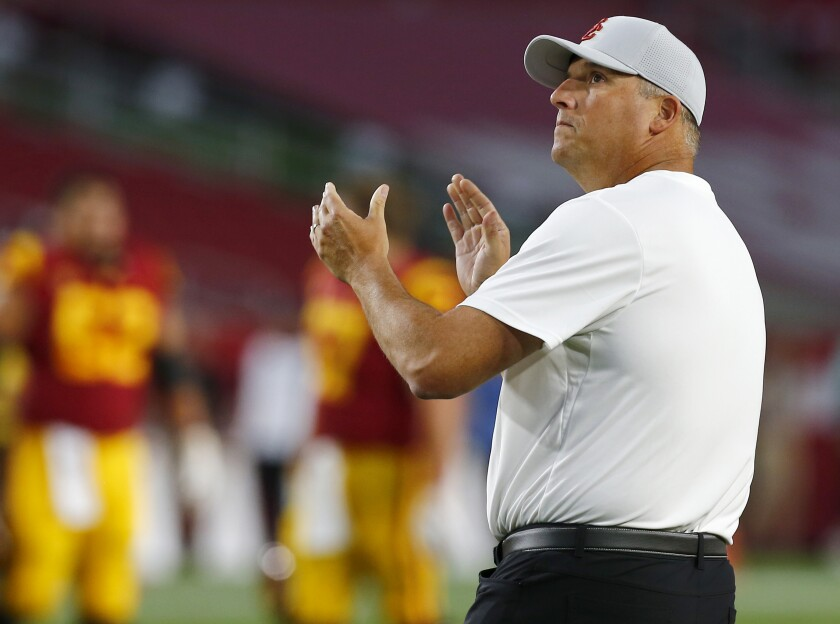 USC coach Clay Helton watches his team warm up before a game against Stanford at the Coliseum on Sept. 7.