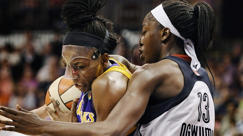 Sparks forward Nneka Ogwumike, left, drives to the basket while being guarded by her sister Chiney Ogwumike of the Connecticut Sun during the Sparks' 90-64 win Sunday.