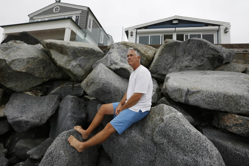 Eric Wills sits on the sea wall in front of his mobile home in Capistrano Shores.