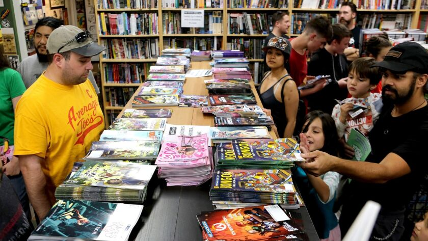 Customers look over free comics at House of Secrets Comics & Toys, on Free Comic Book Day, in Burban