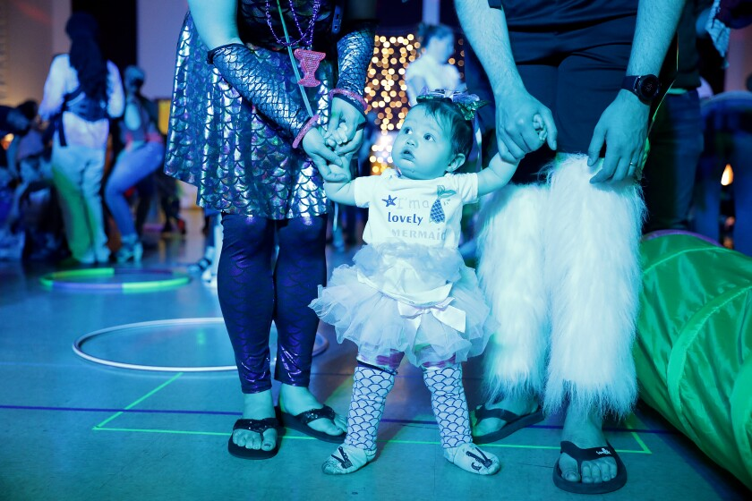 Ariel Harenburg, 10 months, center, attends a baby rave with her parents Carolyn Thamkul, left, and Bryce Harenburg, right, at the Oakland Masonic Center.