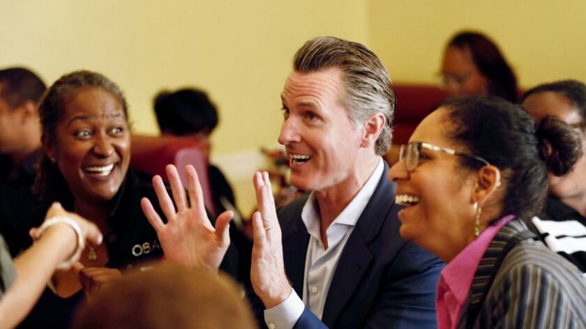 Gavin Newsom with State Sen. Holly Mitchell, left, and Assemblymember Sydney Kamlager-Dove, right, as his bus tour stops at CJ's Cafe on La Brea in Los Angeles before the election.