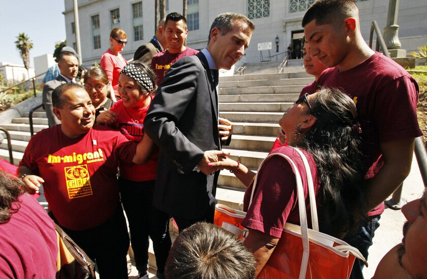 Los Angeles Mayor Eric Garcetti, center, shakes hands with supporters on the steps of City Hall after he and Los Angeles Police Chief Charlie Beck announced in July that the LAPD would no longer comply with requests from federal immigration officials to detain some suspects.