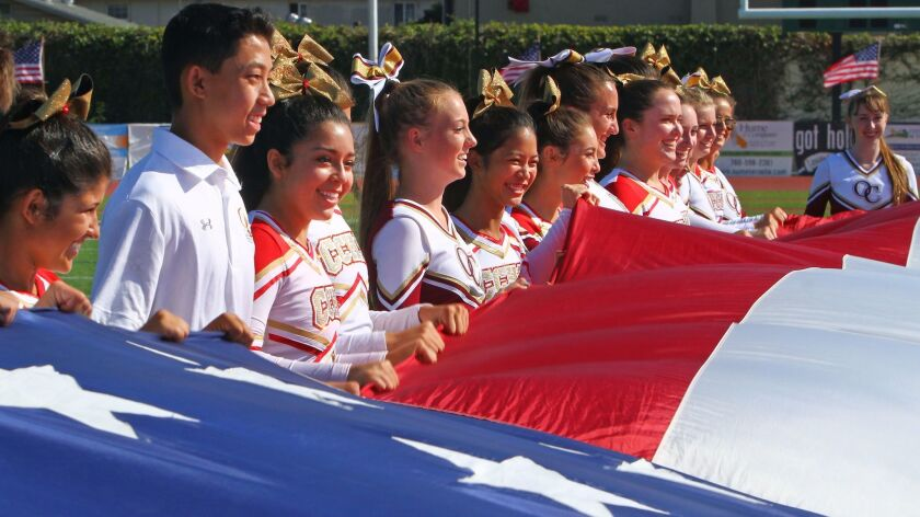 Cathedral Catholic and Oaks Christian cheerleaders display a large American flag before Honor Bowl game in 2017 at Oceanside.