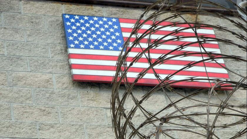 The American flag hangs behind barbed wire at the U.S. Naval Base in Guantanamo Bay, Cuba. Supreme Court Justice Stephen G. Breyer has suggested that the indefinite detention of enemy combatants at Guantanamo may violate the U.S. Constitution.