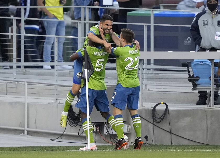 Seattle Sounders midfielder Cristian Roldan, top, celebrates with Nouhou Tolo (5) and Kelyn Rowe (22) after scoring a goal against the San Jose Earthquakes during the first half of an MLS soccer match Wednesday, May 12, 2021, in San Jose, Calif. (AP Photo/Tony Avelar)