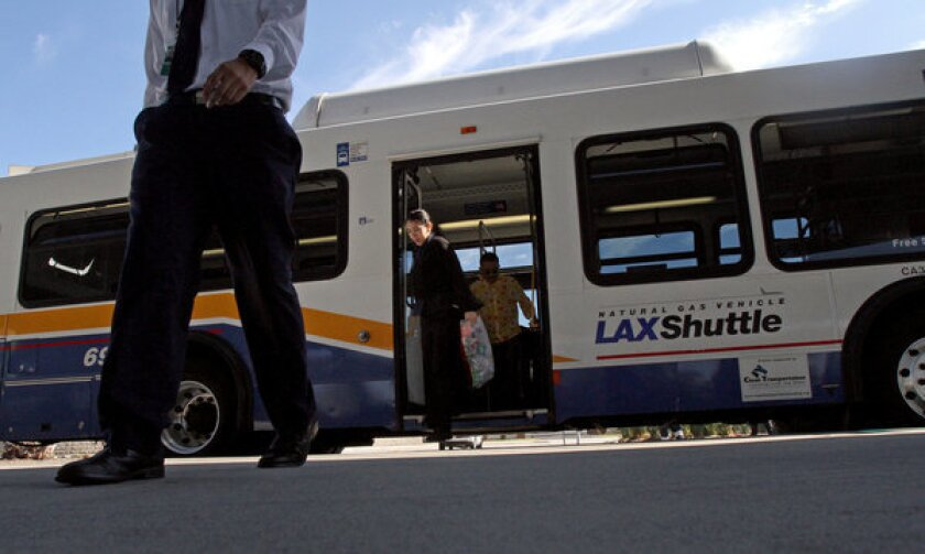 Airport employees get off the LAX Shuttle bus in Los Angeles.