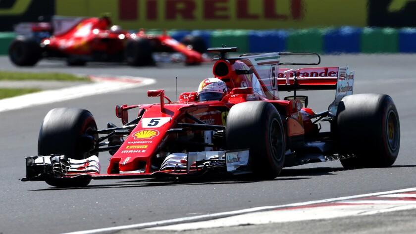 Ferrari driver Sebastian Vettel of Germany steers his car followed by teammate Ferrari driver Kimi R