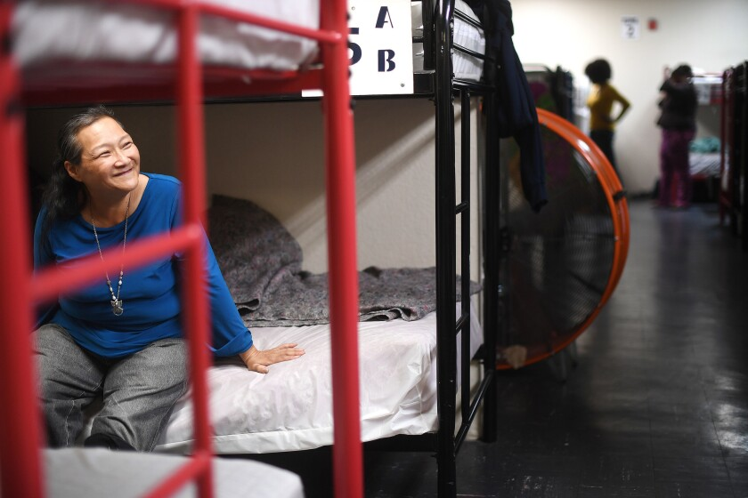 Barbara Siemens, 58, rests on her bunk bed at a women's shelter run by Volunteers of America in Los Angeles. The shelter is one of the biggest women's shelters in L.A.