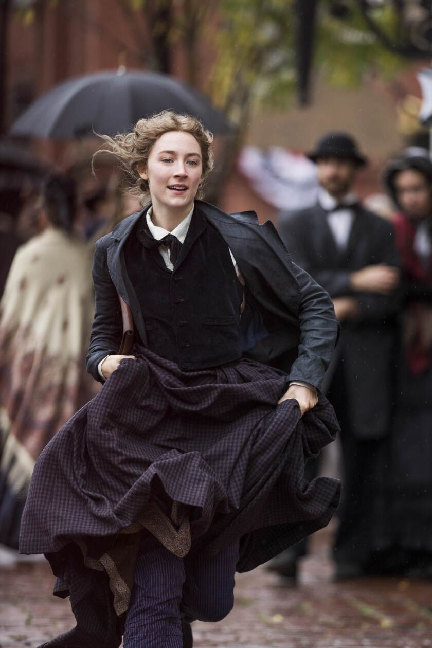 "Saoirse Ronan runs through the street in a scene from ""Little Women."""