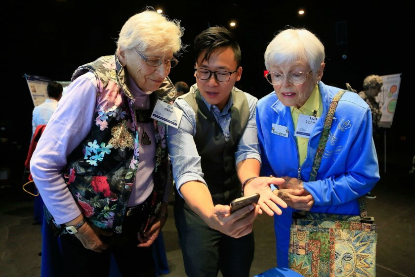 SAN DIEGO, CA-JUNE 4, 2016: |  Jun Lu, center, an electrical engineering major at UCSD demonstrates on his phone a prototype for a concealed wearable exoskeleton designed to detect and react to a human's falling motion to Sue Rosen, left, and Lois Lighthart, right, of La Costa Glen retirement commu