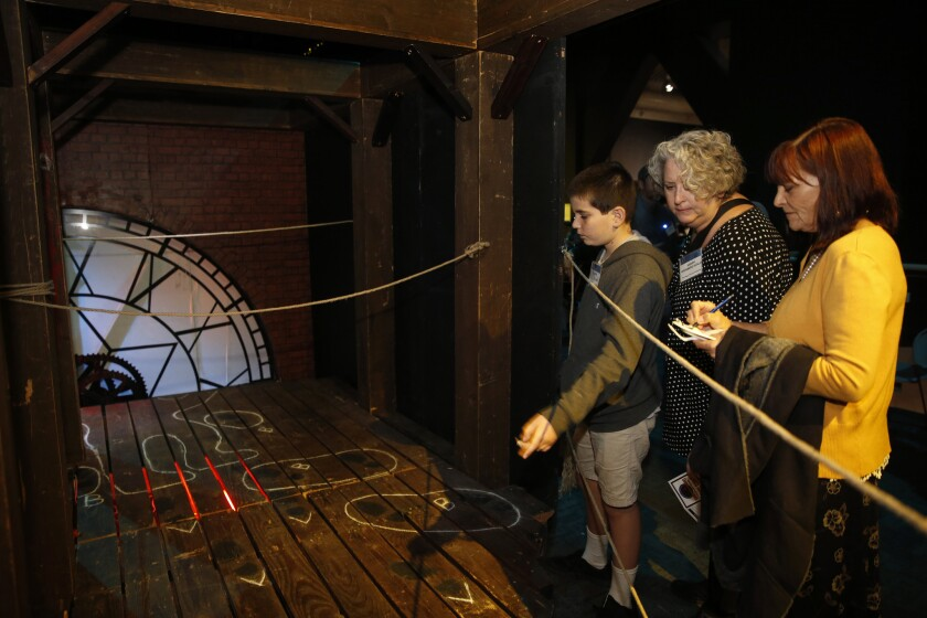 """Andelo Scalo (left), Sarah Weinberg Scalo and Meredith MacCraken look over a crime scene as they follow clues at a sneak peek party for """"Sherlock Holmes and the Clocktower Mystery,"""" a new interactive exhibit at the Fleet Science Center."""