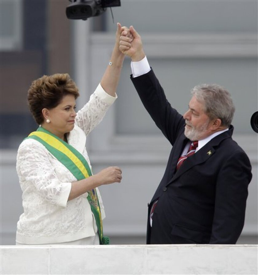 Brazil´s outgoing President Luiz Inacio Lula da Silva, right, raises the arm of Brazil's President Dilma Rousseff after placing the presidential sash on her at the Planalto palace in Brasilia, Brazil, Saturday, Jan. 1, 2011. Rousseff, a former rebel who was imprisoned and tortured during the nation's 21-year military dictatorship, was sworn in as Brazil's first female president Saturday.(AP Photo/Silvia Izquierdo)