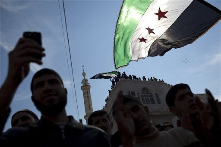 Men hold revolutionary Syrian flags during an anti government protest in a town in north Syria, Friday, March 2, 2012. Syria has faced mounting international criticism over its bloody crackdown on the uprising, which started with peaceful protests but has become increasingly militarized. (AP Photo/Rodrigo Abd)
