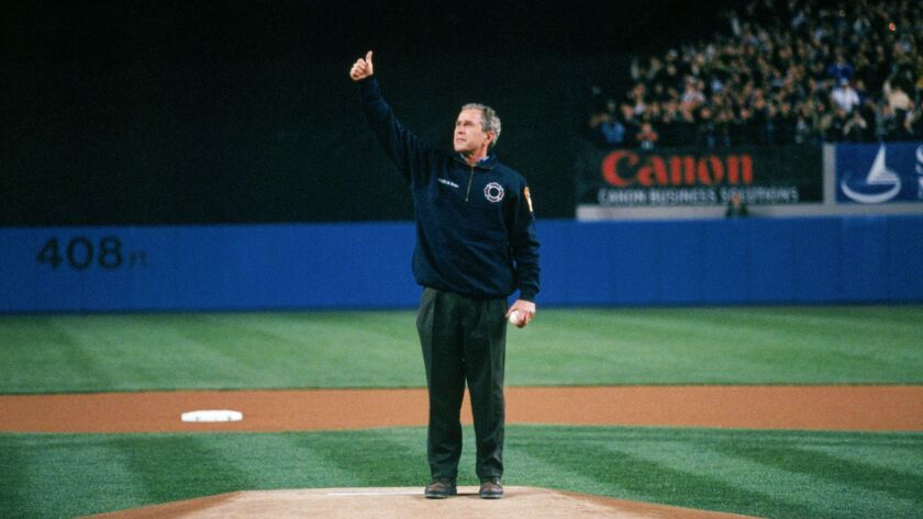 President George W. Bush gives a thumbs up at the ceremonial first pitch prior ot Game Three of the