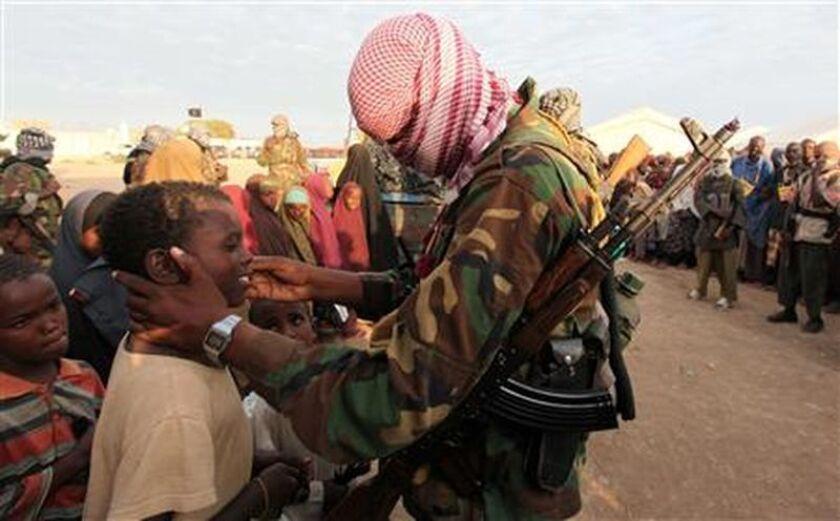 Un integrante de Al Shabaab —insurgentes ligados a al Qaeda— conversa con niños refugiados somalíes en Ala Yaasir.