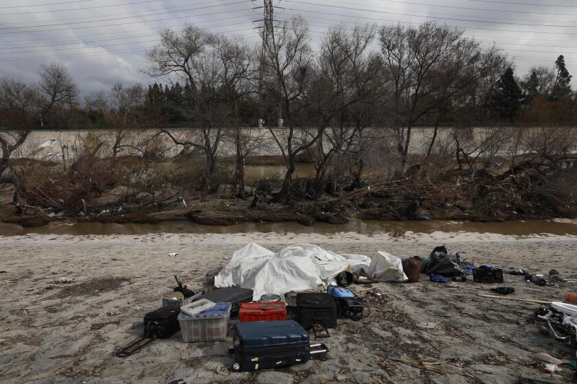 Suitcases, boxes and other items next to a stream.